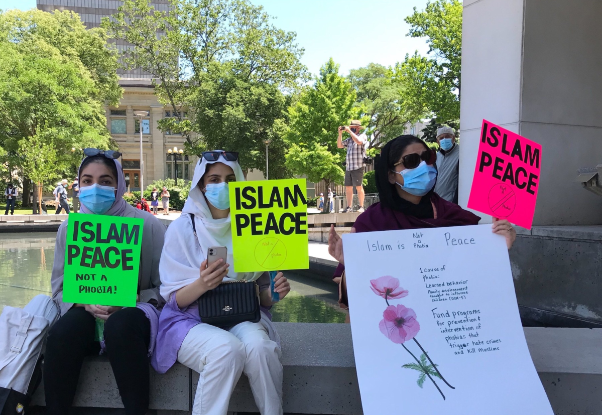 Attendees of a vigil in front of Hamilton city hall hold signs condemning Islamophobia following the attack on a Muslim family in London last month.