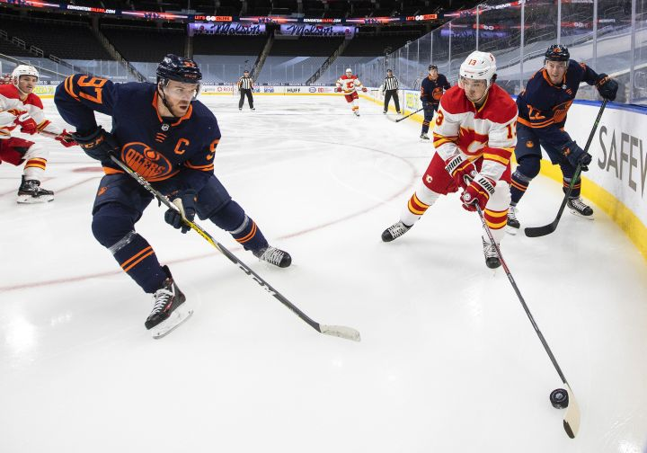 Edmonton Oilers' Connor McDavid (97) and Calgary Flames' Johnny Gaudreau (13) battle for the puck during first period NHL action in Edmonton on Saturday, May 1, 2021.