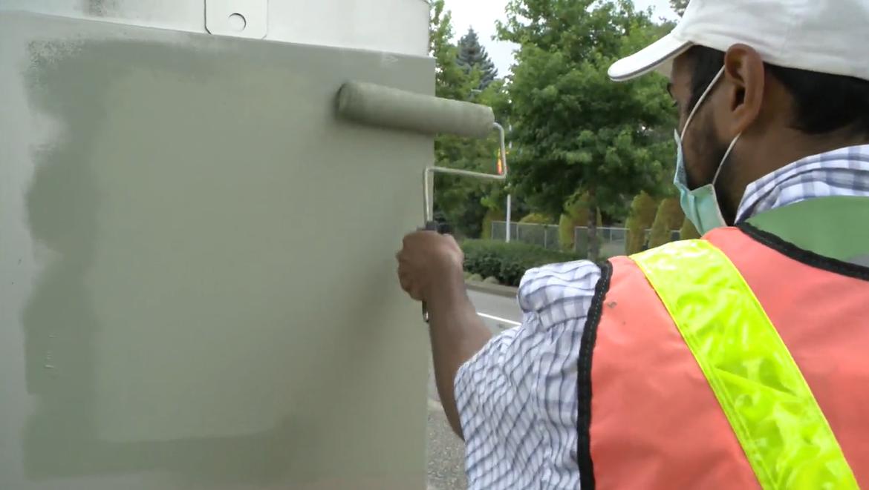 Volunteer Jaspreet Jandu paints over graffiti in Surrey. Police say they've had multiple reports of anti-Muslim graffiti in the Newton area in recent weeks.