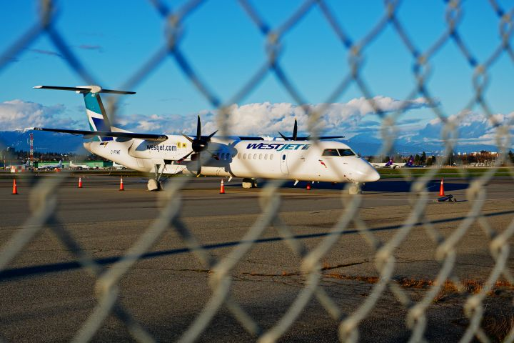 A WestJet Encore DeHavilland Canada Dash 8-400 turboprop regional airliner (C-FKWE) parked and stored at the south terminal of Vancouver International Airport, Richmond, B.C. on Monday, March 22, 2021.