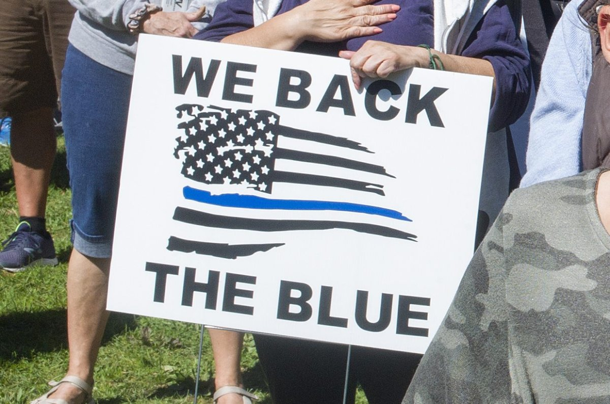 In this file photo, a protester holds a 'Back the Blue' sign at a demonstration in Malverne, N.Y., on Sept. 19, 2020.
