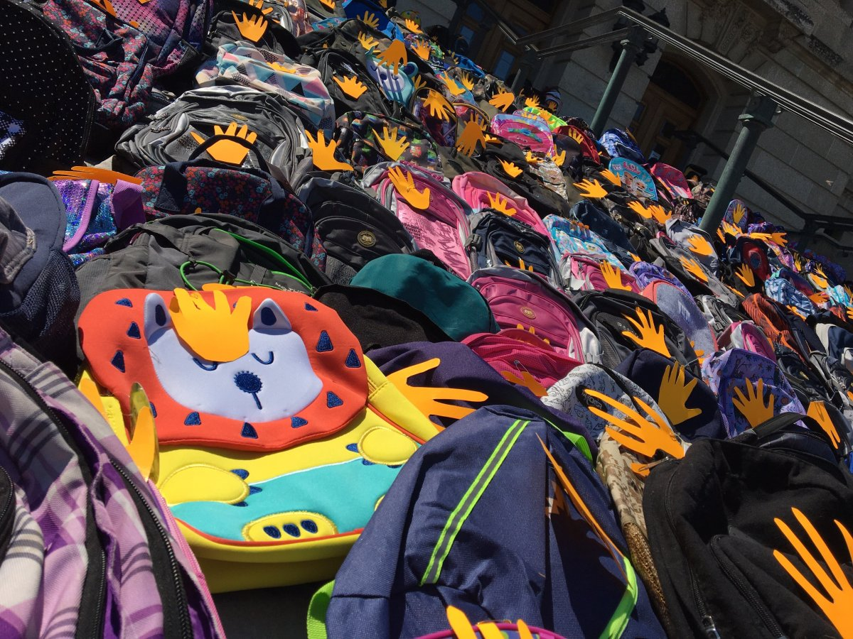 Hundreds of backpacks line the steps of the provincial legislative building to represent unmarked graves found at residential schools.
