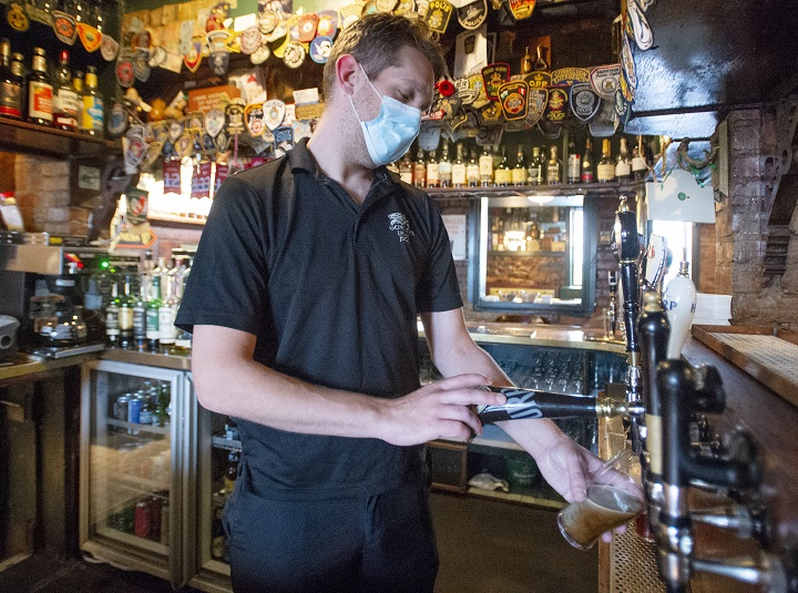 Bartender Neil Creighton pulls a pint of beer at Hurley's Pub Wednesday, September 30, 2020  in Montreal.