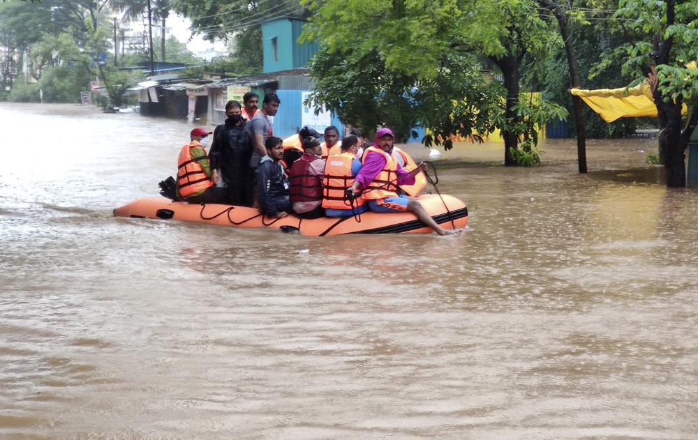 National Disaster Response Force personnel rescue people stranded in floodwaters in Kolhapur, in the western Indian state of Maharashtra, Friday, July 23, 2021. Landslides triggered by heavy monsoon rains hit parts of western India, killing more than 30 people and leading to the overnight rescue of more than 1,000 other people trapped by floodwaters, officials said Friday.