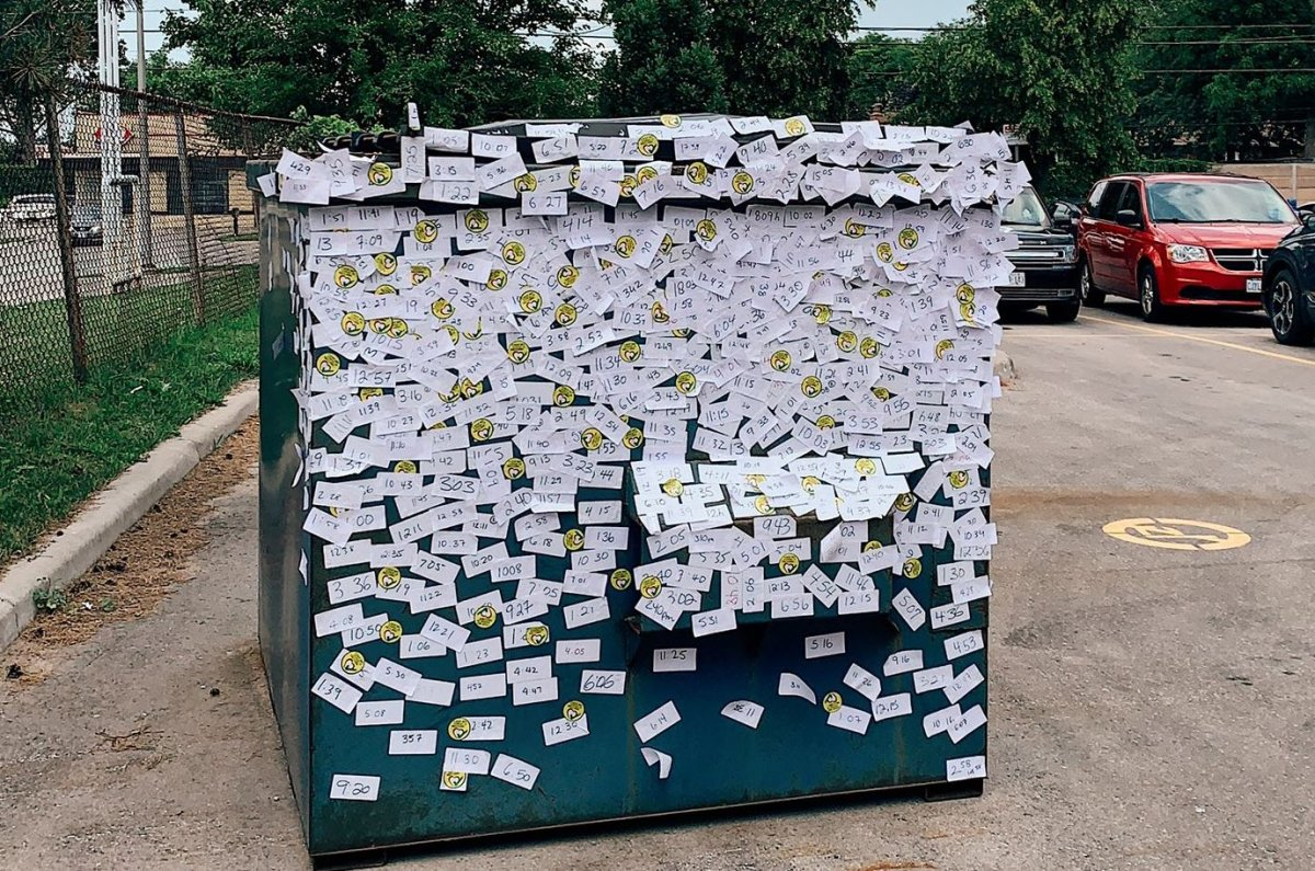 A dumpster outside of the North London Optimist Community Centre mass vaccination clinic in London, Ont., is covered with stickers showing what time vaccinated people are able to leave as well as stickers to mark full vaccination in July 2021.