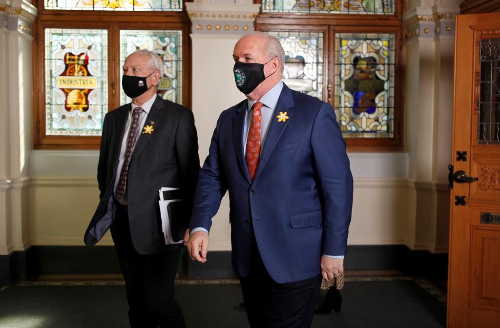Minister of Indigenous Relations and Reconciliation Murray Rankin, left, and Premier John Horgan leave the chamber at the Legislature in Victoria, B.C., on April 12, 2021. THE CANADIAN PRESS/Chad Hipolito.
