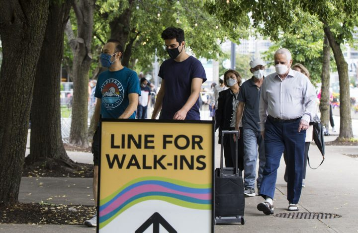 People line up to enter a vaccination clinic in Mel Lastman Square in Toronto on July 24, 2021.