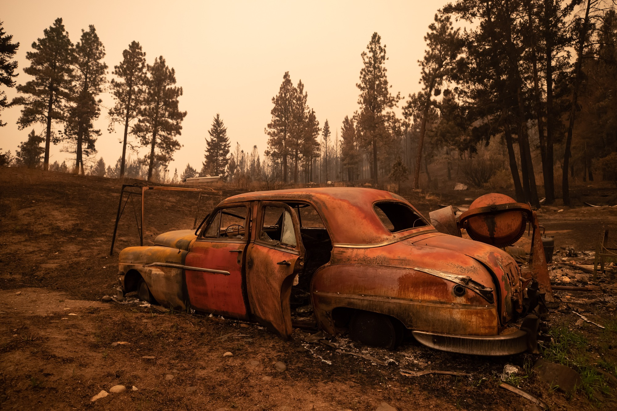 The remains of a classic car is seen on a property destroyed by the White Rock Lake wildfire in Monte Lake, east of Kamloops, B.C., on Saturday, August 14, 2021. THE CANADIAN PRESS/Darryl Dyck.