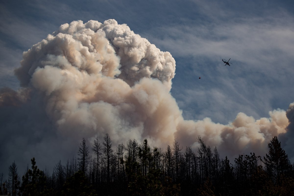 A helicopter carrying a water bucket flies past a pyrocumulus cloud, also known as a fire cloud, produced by the Lytton Creek wildfire burning in the mountains above Lytton, B.C., on Sunday, August 15, 2021.
