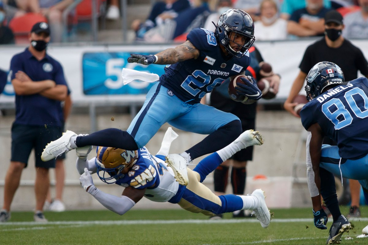 Toronto Argonauts D.J. Foster (29) avoids a tackle by Winnipeg Blue Bombers defensive back DeAundre Alford (45) during first half CFL football action in Toronto, Saturday, Aug. 21, 2021.