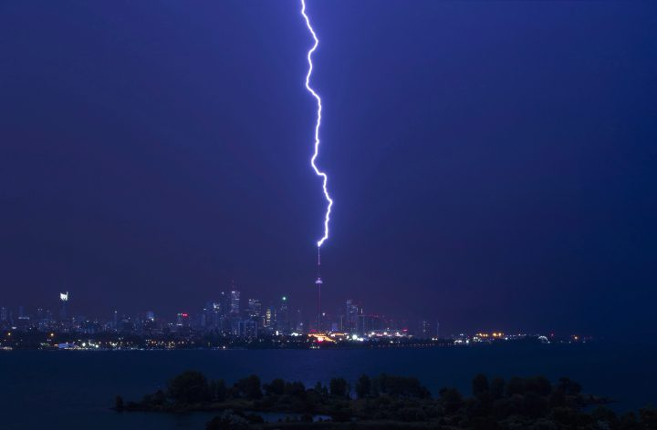 A lightning bolt strikes the CN Tower during an electrical storm in Toronto, early Thursday July 14, 2016.