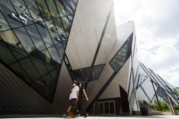 People wearing masks walk by the  Royal Ontario Museum in Toronto, on Friday, June 26, 2020.