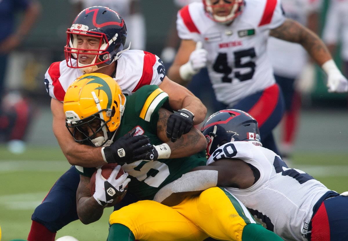 Montreal Alouettes' Christophe Normand (38) and Jeshrun Antwi (20) tackle Edmonton Elks' Terry Williams (5) during second half CFL action in Edmonton, Alta., on Saturday August 14, 2021.