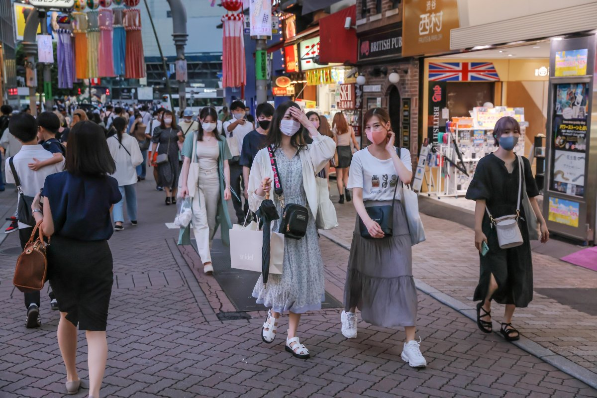 Pedestrians wearing face masks as a precaution against the spread of COVID-19 walk in the streets of Shibuya, amid the COVID-19 pandemic.