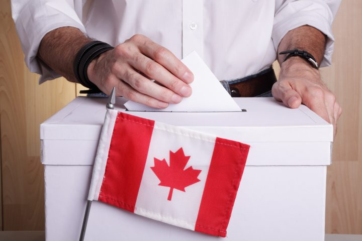 A man casting his vote. The Canadian flag is in front of the ballot box.