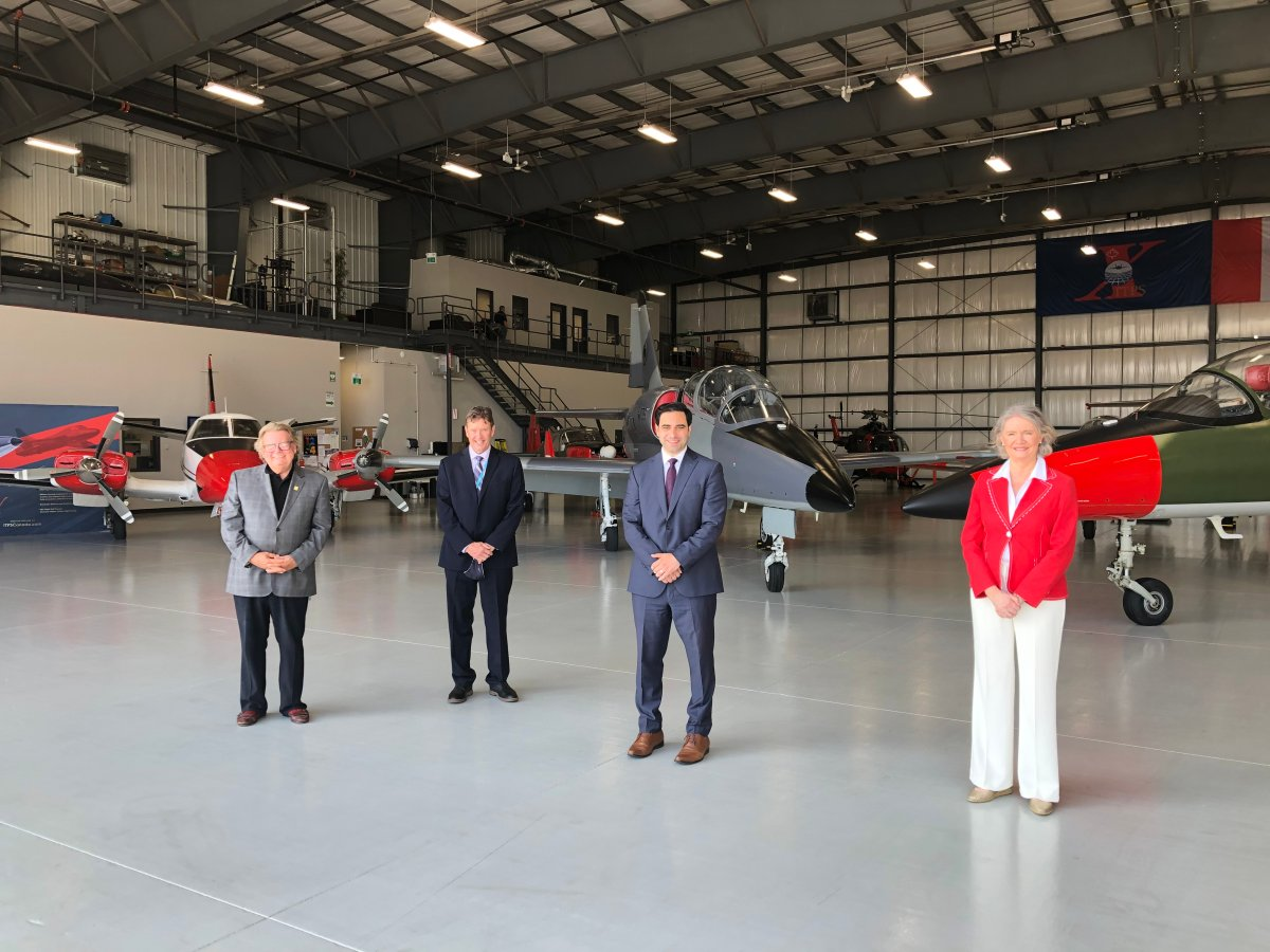 From left to right: Mayor Ed Holder, London International Airport president and CEO Mike Seabrook, London North Centre MP Peter Fragiskatos and London West MP Kate Young stand inside one of several hangars at the airport.