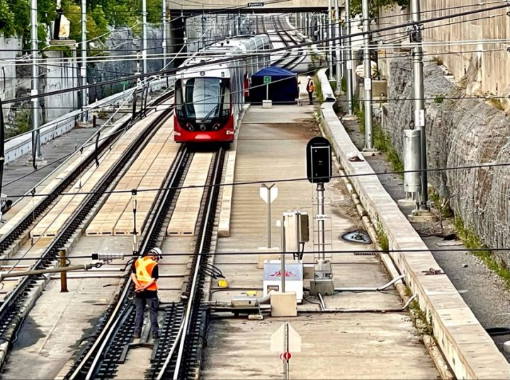 Crews inspect the damaged Confederation Line train just east of Tunney's Pasture station on Monday, Aug. 9.