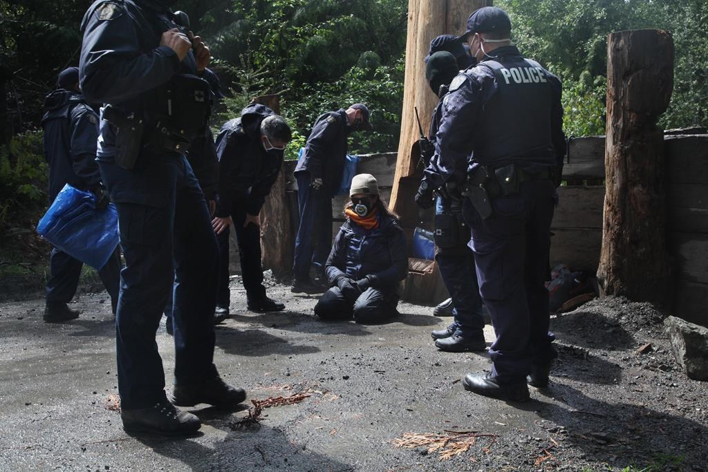 """Police speak with a man who calls himself """"UDI"""" after breaking the chain that held him to a stump during an anti-logging blockade in Caycuse, B.C., Tuesday, May 18, 2021. The RCMP's enforcement of a B.C. Supreme Court injunction against blockades set up to prevent old-growth logging on Vancouver Island continued this weekend. THE CANADIAN PRESS/Jen Osborne."""