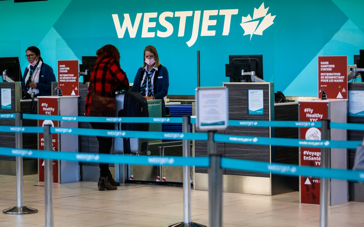 A passenger checks in at a Westjet counter at  the Calgary Airport in Calgary, Alta., Friday, Oct. 30, 2020, amid a worldwide COVID-19 pandemic.