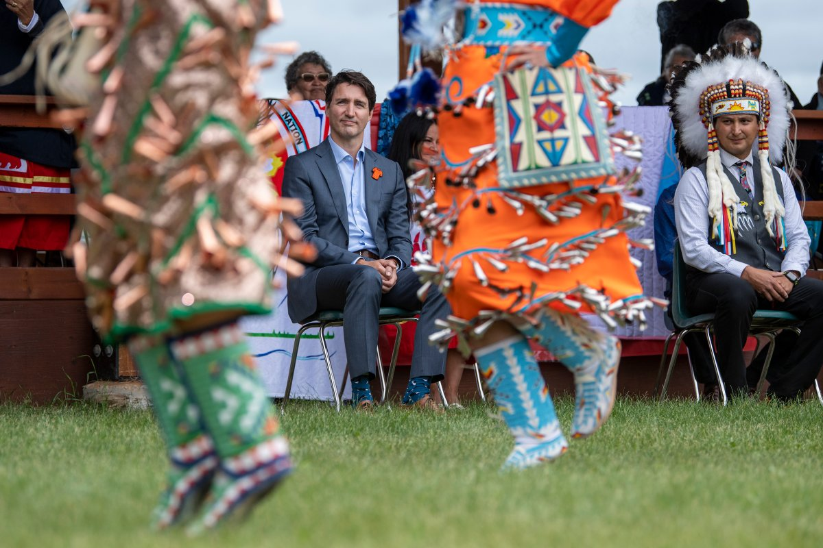 Prime Minister Justin Trudeau, left, and Chief Cadmus Delorme watch dancers during a ceremony celebrating the signing of a transfer of control over children in care to the community, in Cowessess First Nation, Sask., Tuesday, July 6, 2021.  THE CANADIAN PRESS/Liam Richards.