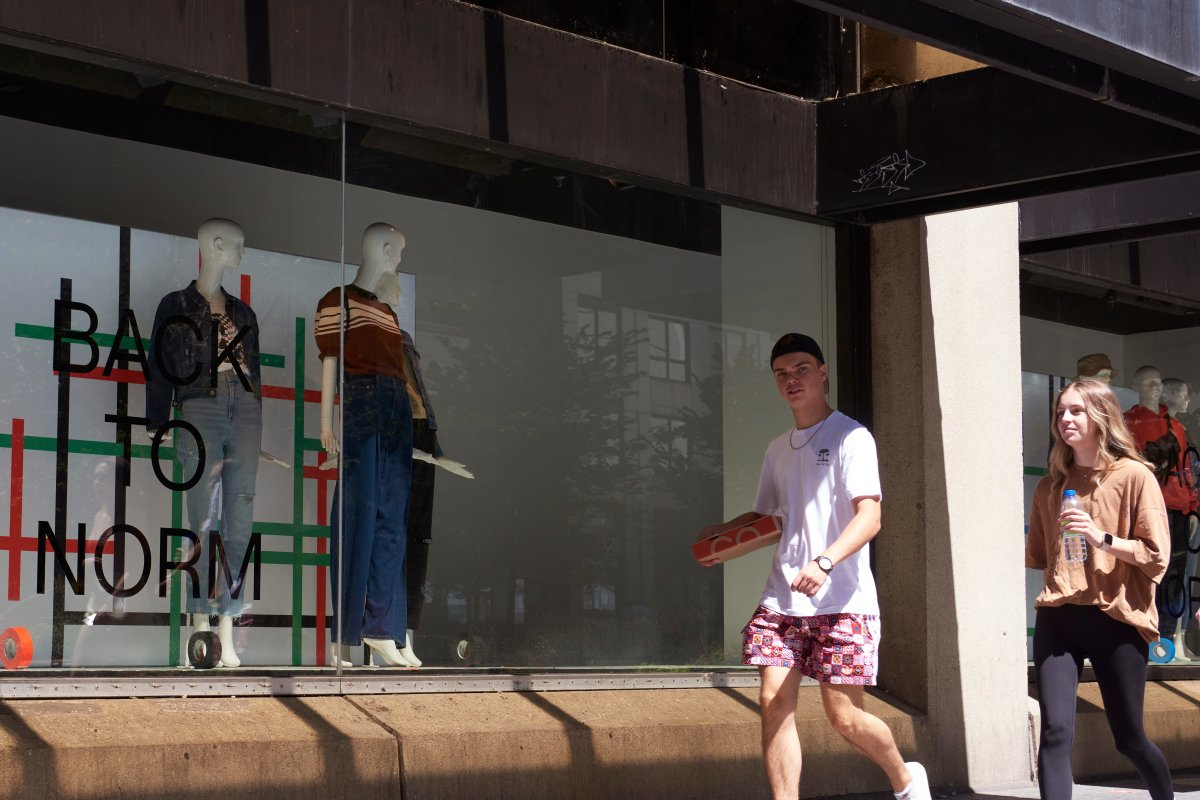 Young adults carrying takeout food walk past a 'BACK TO NORM' Hudson's Bay window display on Bloor Street in Toronto on Aug. 15, 2021, as Ontario enters a fourth wave of the COVID-19 pandemic.
