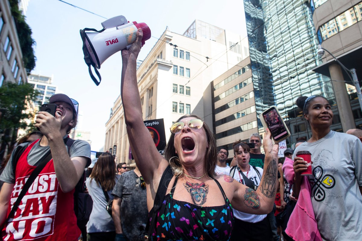 Protesters listen to a speaker as they gather outside Toronto Police Headquarters to voice opposition to COVID-19 vaccines and other COVID-19 related restrictions on Thursday September 2, 2021. THE CANADIAN PRESS/Chris Young.