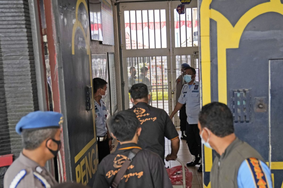 Staff and police officers guard the main entrance gate of Tangerang prison in Tangerang on the outskirts of Jakarta, Indonesia, Wednesday, Sept. 8, 2021. A massive fire raged through the overcrowded prison early Wednesday, killing a number of inmates. (AP Photo/Dita Alangkara).