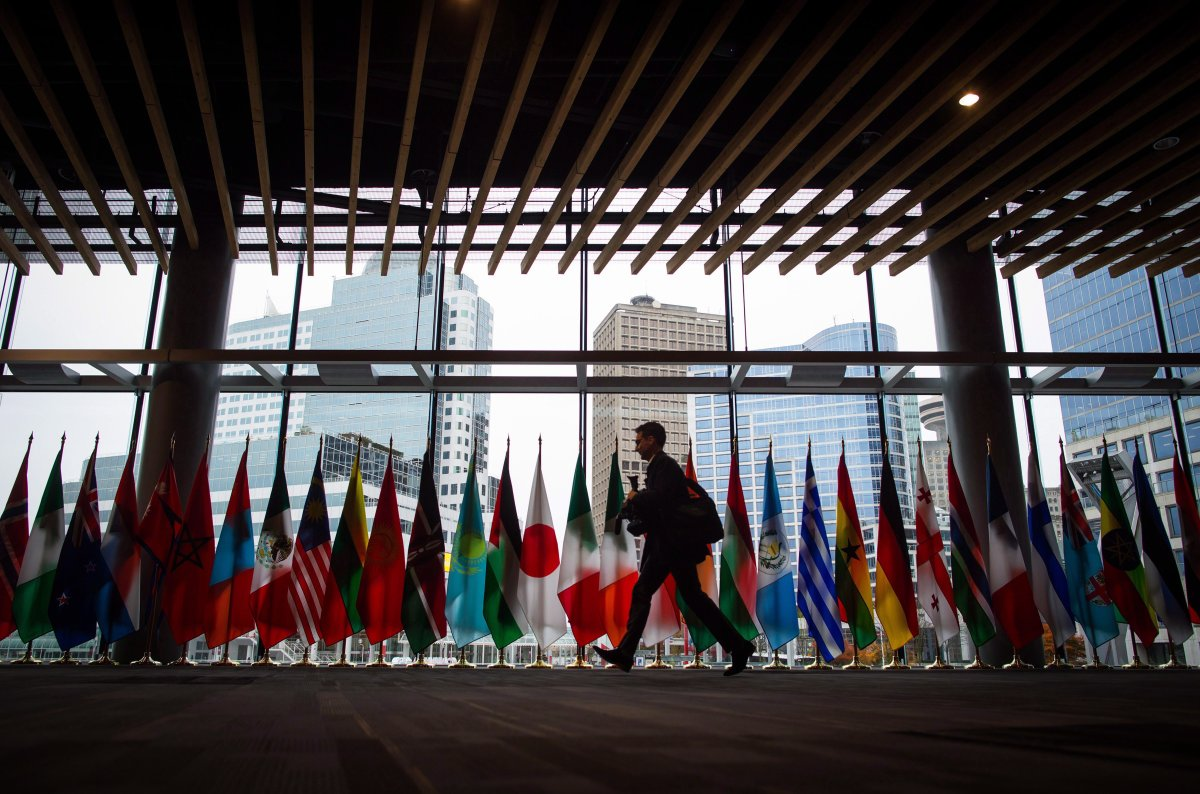 A man walks past the flags of participating nations at the 2017 United Nations Peacekeeping Defence Ministerial conference in Vancouver, B.C., on Tuesday November 14, 2017. The two-day conference is largest gathering of defence ministers dedicated to UN peacekeeping.