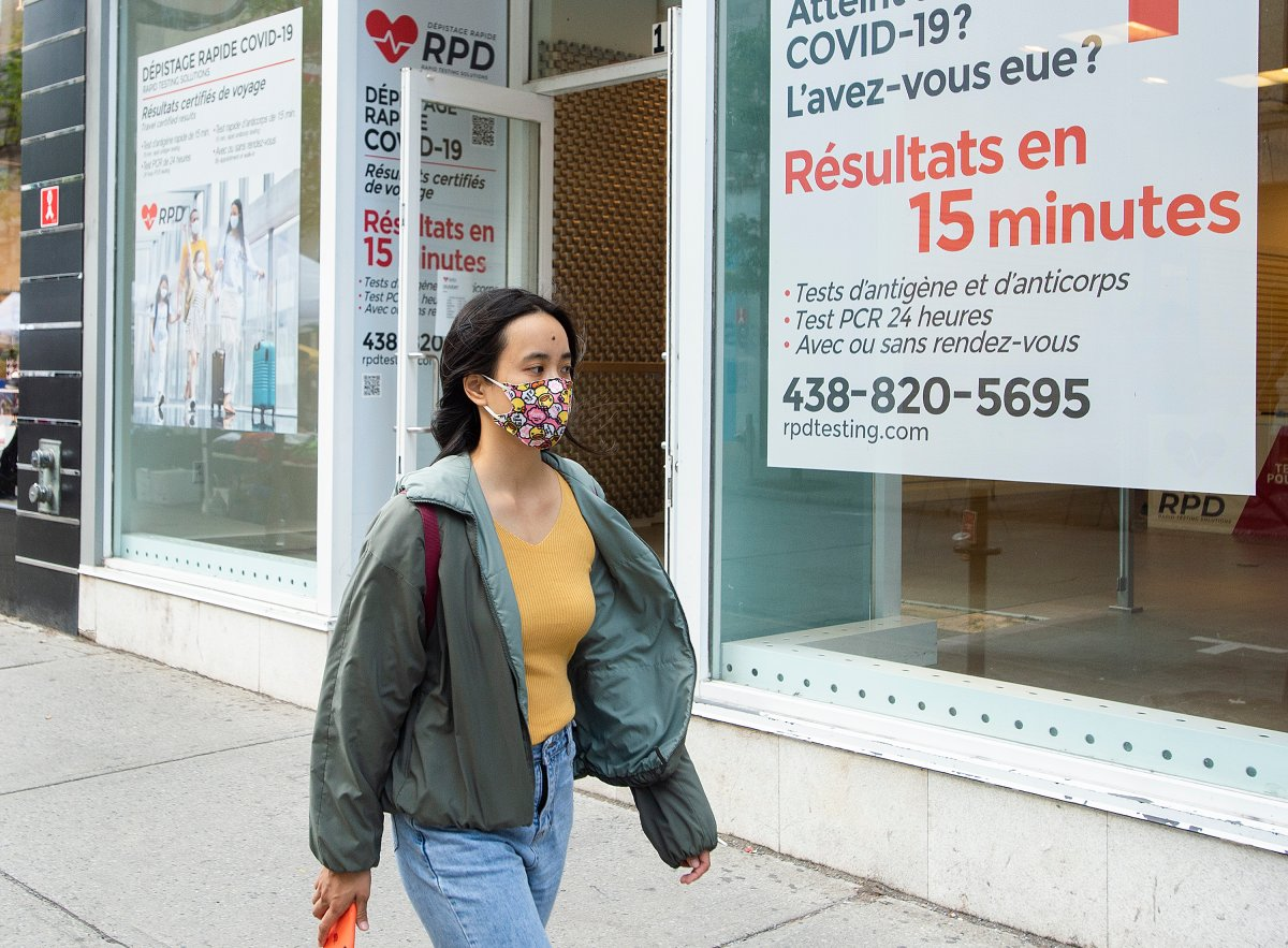 A woman wears a face mask as she walks by a COVID-19 rapid testing clinic in Montreal, Sunday, September 12, 2021, as the COVID-19 pandemic continues in Canada and around the world.