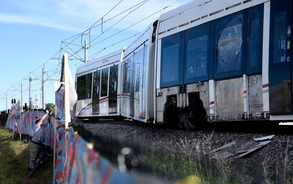 A window is broken and the wheels of a segment of an OC Transpo O-Train is seen west of Tremblay LRT Station  in Ottawa on Monday, Sept. 20, 2021 after it derailed on Sunday. The train has since been moved back to the storage yard.
