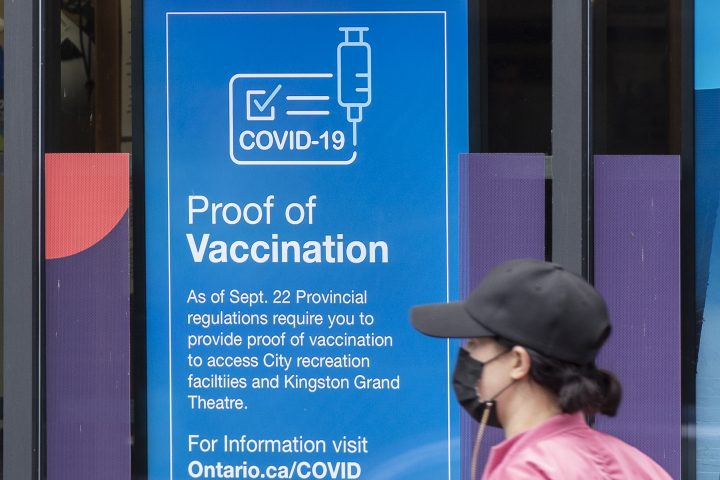 A person wears a mask to protect them from the COVID-19 virus while walking past information about vaccination proof on Thursday September 23, 2021.
