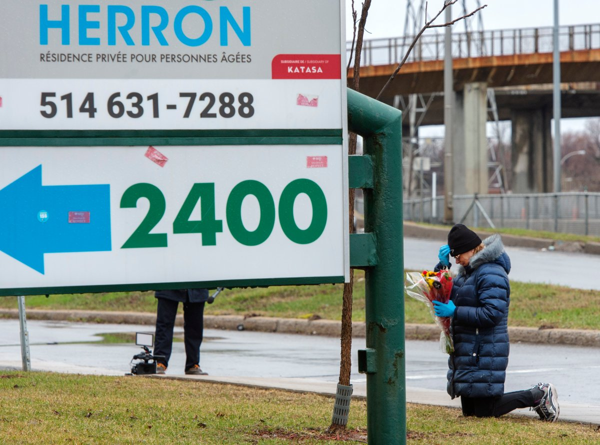 A woman prays in front of the Herron seniors residence Monday April 13, 2020 in Dorval near Montreal's Trudeau airport.