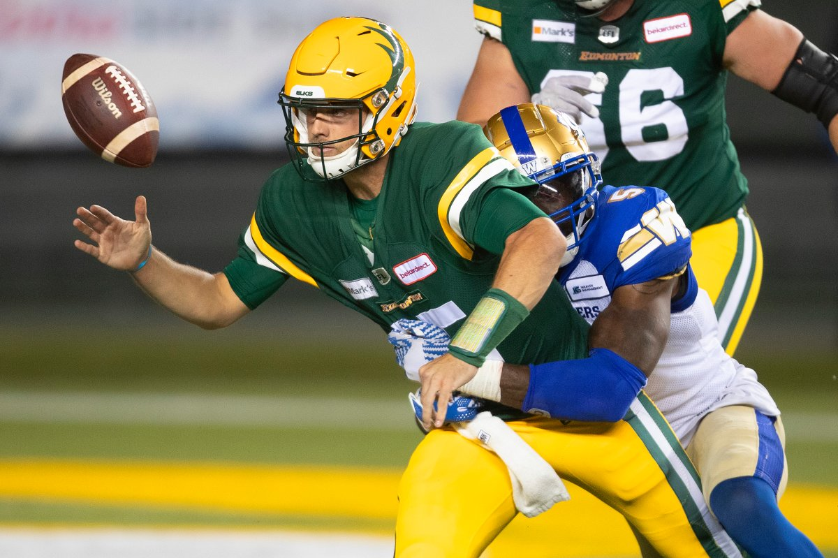 Winnipeg Blue Bombers Willie Jefferson (5) knocks the ball loose from Edmonton Elks quarterback Taylor Cornelius (15) during second half CFL action in Edmonton, Alta., on Saturday September 18, 2021.