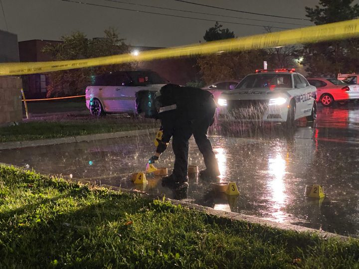 A police officer places evidence markers at the scene of a fatal shooting in Mississauga on Wednesday.