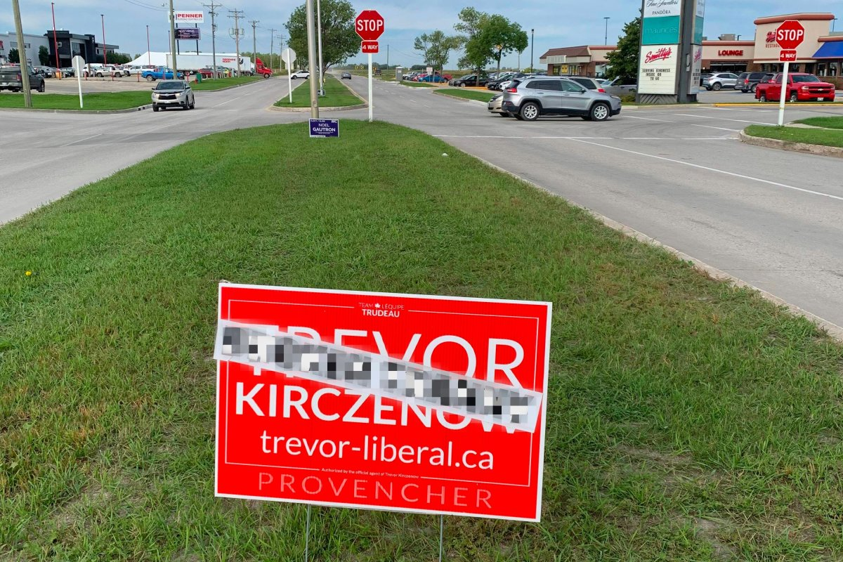 A blurred photo of Trevor Kirczenow's election signs featuring stickers with what he says are transphobic comments.