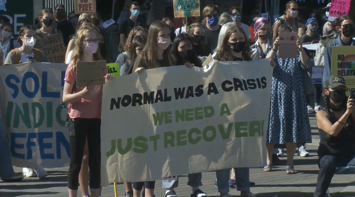 Youth hold a sign calling for a green COVID-19 recovery at a protest in Vancouver on Friday.